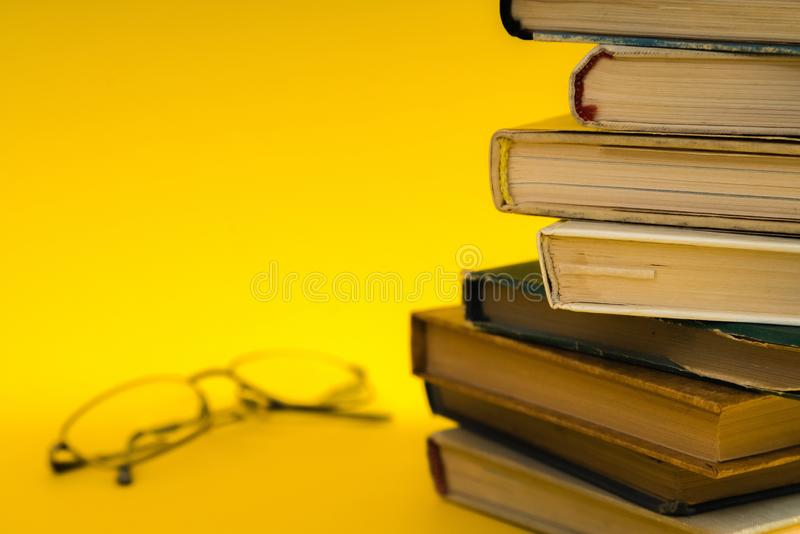 Open book, hardback hard cover colorful books with reading glass. Es on the side. Back to school. Copy space for text. Education, studying, learning, business stock photos