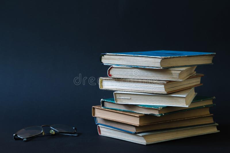 Open book, hardback hard cover colorful books with reading glass. Es on the side. Back to school. Copy space for text. Education, studying, learning, business stock photography