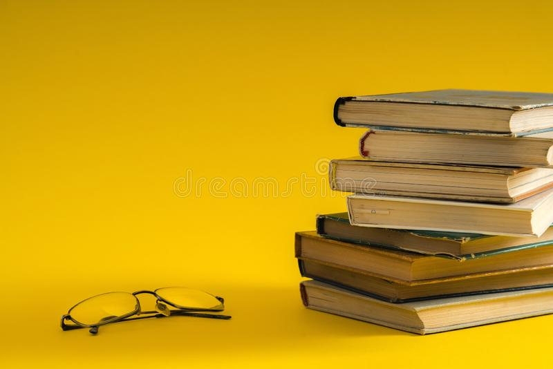 Open book, hardback hard cover colorful books with reading glass. Es on the side. Back to school. Copy space for text. Education, studying, learning, business stock photo