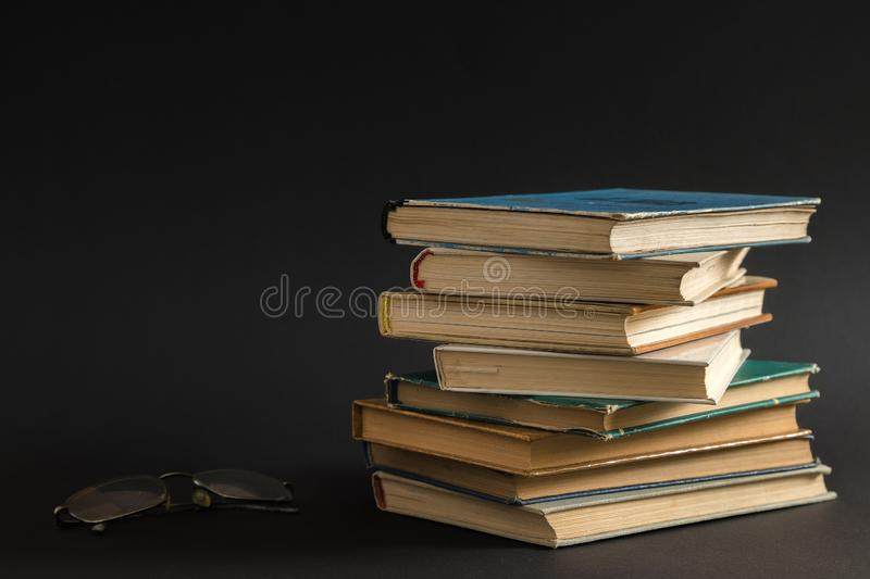 Open book, hardback hard cover colorful books with reading glass. Es on the side. Back to school. Copy space for text. Education, studying, learning, business royalty free stock photo