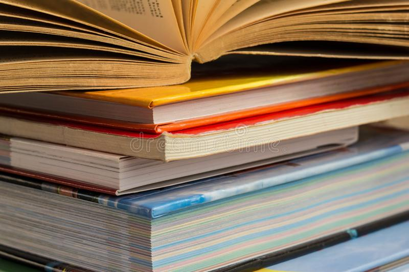 Open book on heap of closed books, study and teaching concept stock photo