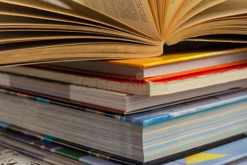 Open book on heap of closed books, study and teaching concept royalty free stock photos