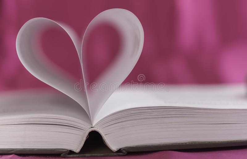 Open book with heart shape stock image