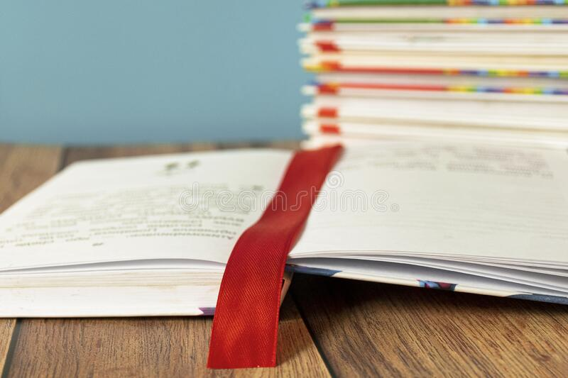 An open book lies on a table with a bookmark for pages. Book binding. Knowledge and education. Books for children. stock image