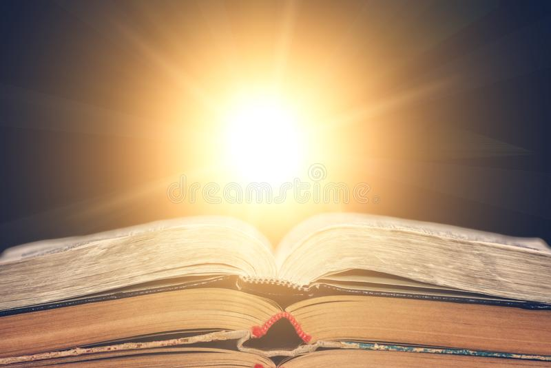 The open book lies on the table and the sun shines from it. Library, the concept of education. Empty place for text. The open book lies on the table and the sun royalty free stock photography