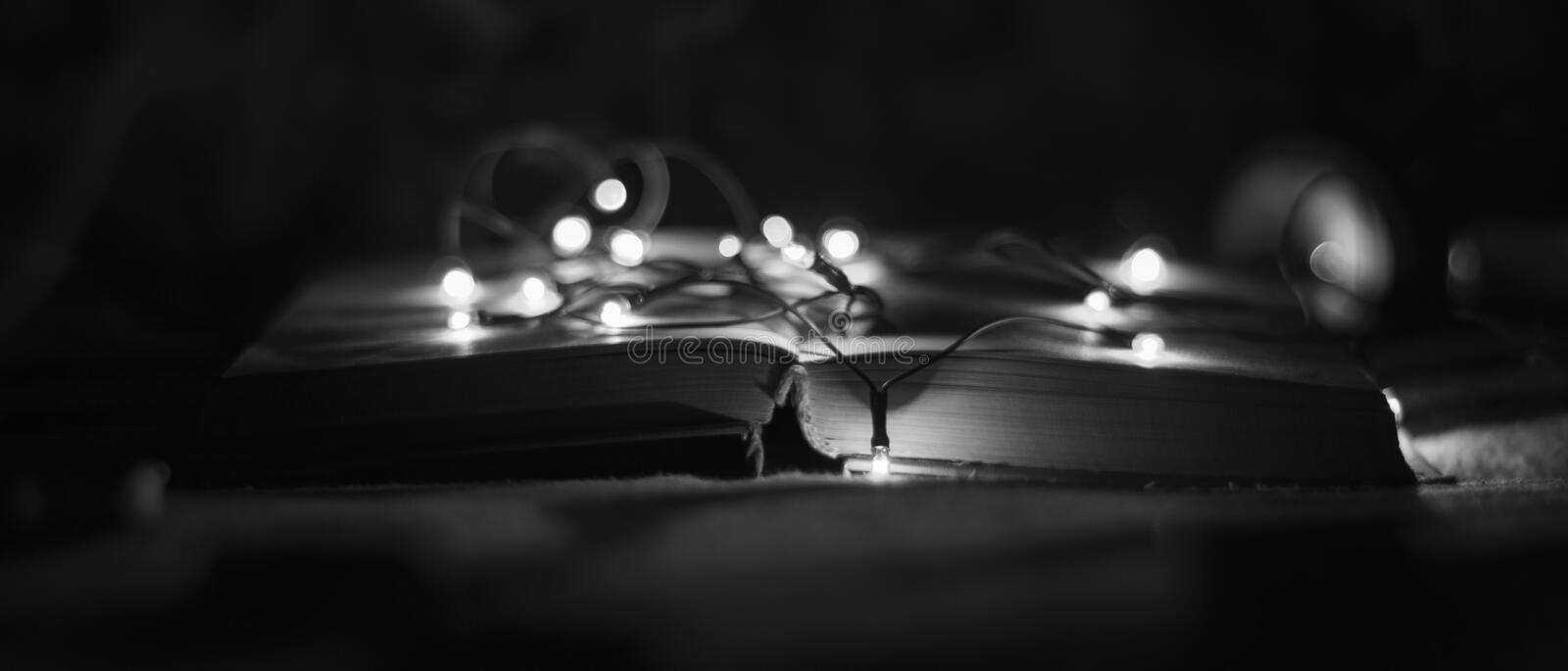 Open book with lights garlands in a black and white style royalty free stock photos