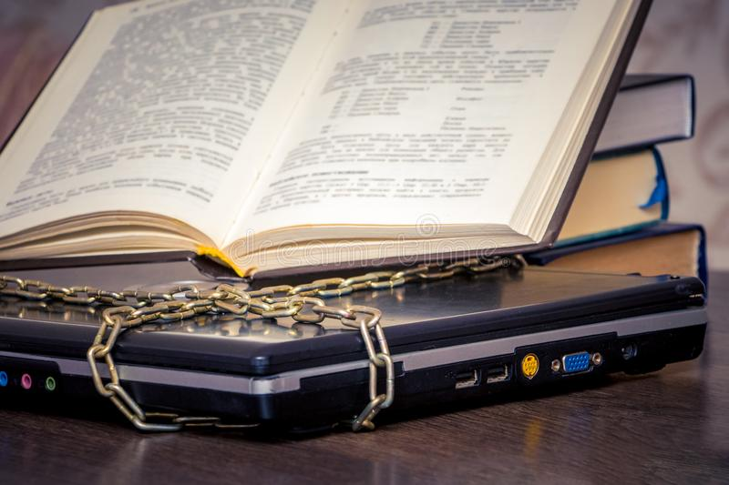 An open book is lying on a laptop that is linked by a chain. Books instead of computers. Love to read_ royalty free stock photo