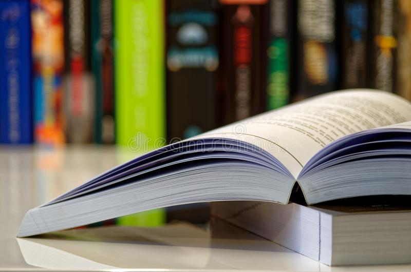Open book lying on the table with colorful books in a row in background. Open book lying on a white table and colorful books in a row in background stock images