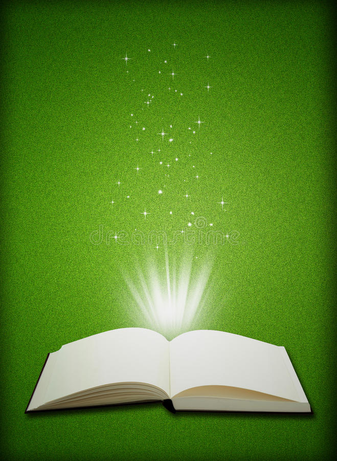 open book magic on green grass background stock photos