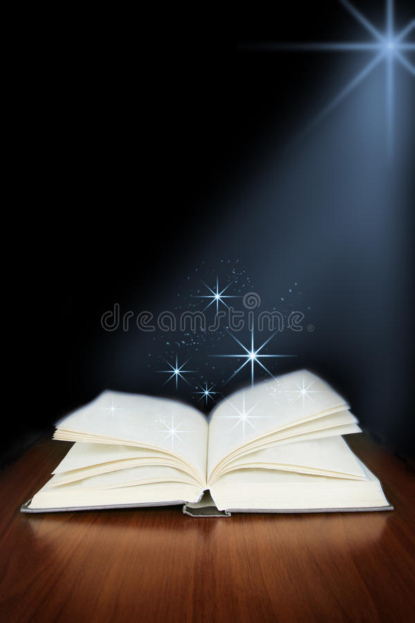 Download open book with magic light on wood planks and stock photo image of education