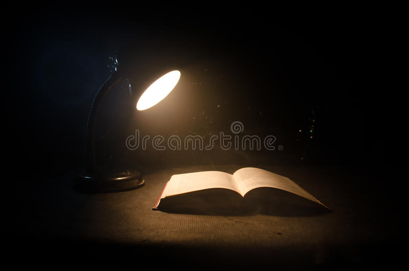 Open book near glowing table lamp on dark background, Lamp and opened book with smoke on background. Surreal. Open book near glowing table lamp on dark stock photo