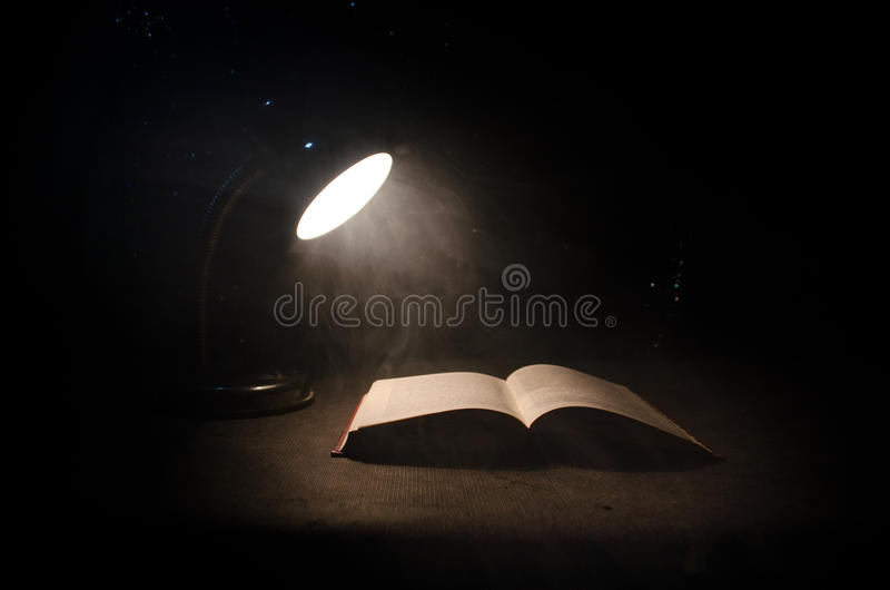 Open book near glowing table lamp on dark background, Lamp and opened book with smoke on background. Surreal. Open book near glowing table lamp on dark stock photos