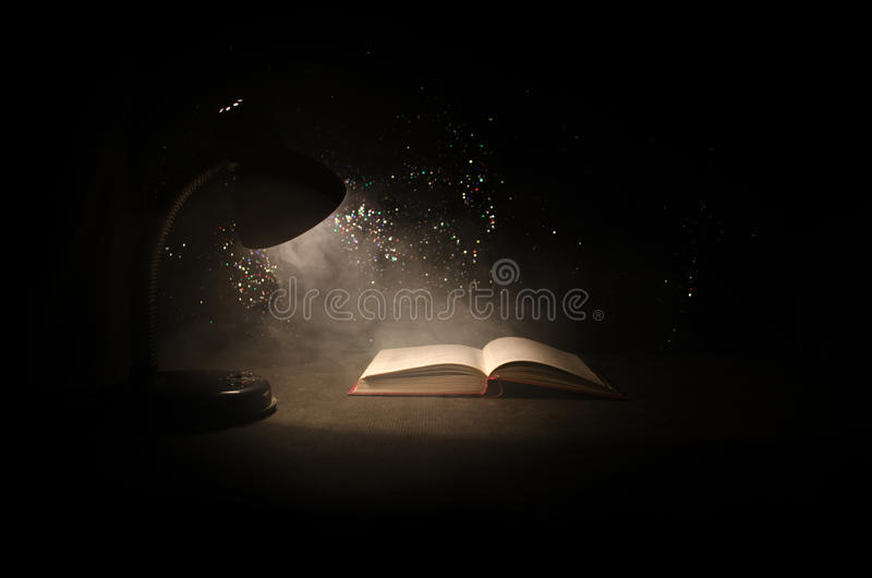 Open book near glowing table lamp on dark background, Lamp and opened book with smoke on background. Surreal. Open book near glowing table lamp on dark royalty free stock photo