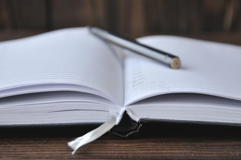 Open book or notebook. On the book is a black pen. stock images