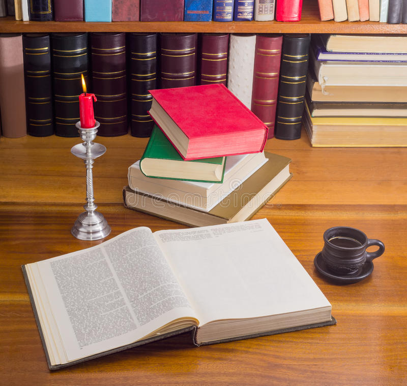 Open book and other books on a table by candlelight stock image