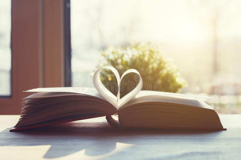 Open book with pages shaped as heart on wooden table royalty free stock photography