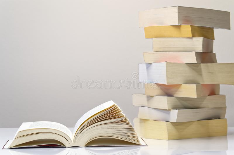 Open book and pile of books on the white table. Open book and pile of books lying on white table with light grey background royalty free stock images