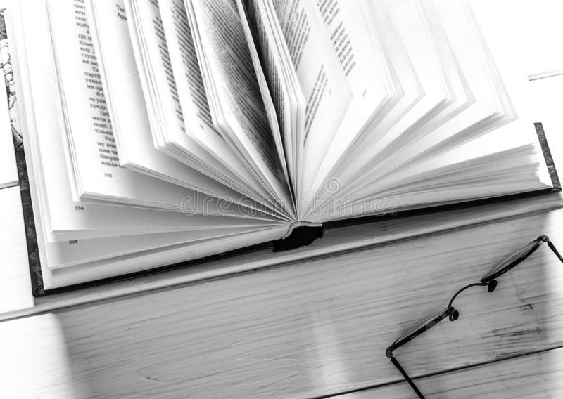 Open book ready to read lies on a white wood table next to the old round glasses. Closeup, background, paper, thick, shop, bookshelf, bookstore, cardboard stock photography