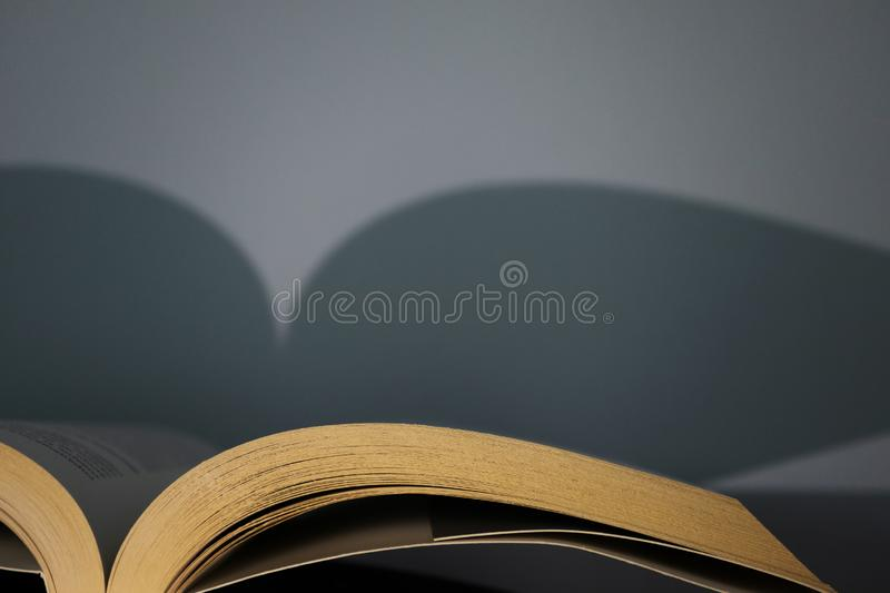 Open book. Shadow from old vintage book on gray wall. Concept of reading, library, education with empty space royalty free stock photography
