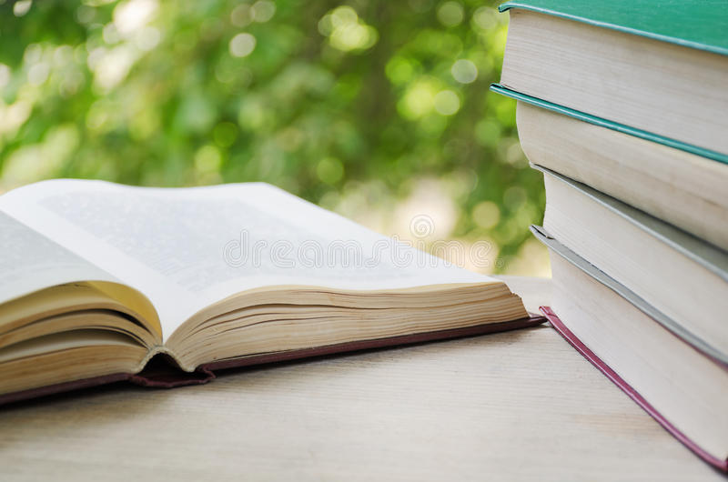Open book and stack of books on the background of a window with greens. royalty free stock photos