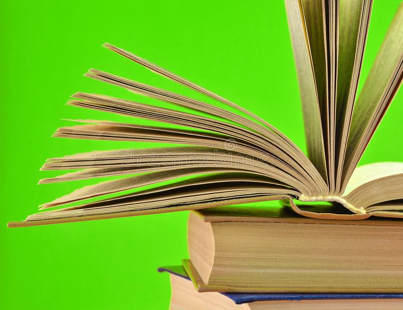 Open book, a stack of books isolated on green background. Open book, a stack of books isolated on a yellow background. Copy space, pastel color trend royalty free stock photography