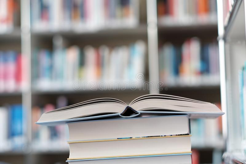 Open book on stack of books in a library. Open book on a stack of books in a library, shelf, read, white, education, study, school, learn, yellow, information royalty free stock photography