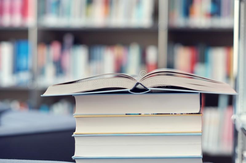 Open book on a stack of books in a library. Open book on a stack of books on a table in a library, shelf, read, white, education, study, school, learn, yellow royalty free stock images