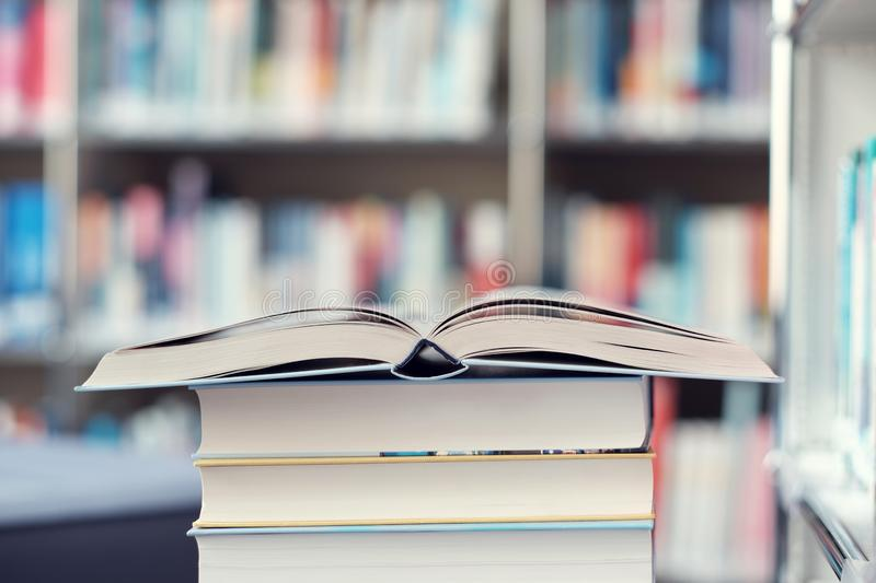 Open book on a stack of books in a library. Open book on a stack of books on a table in a library, shelf, read, white, education, study, school, learn, yellow royalty free stock image