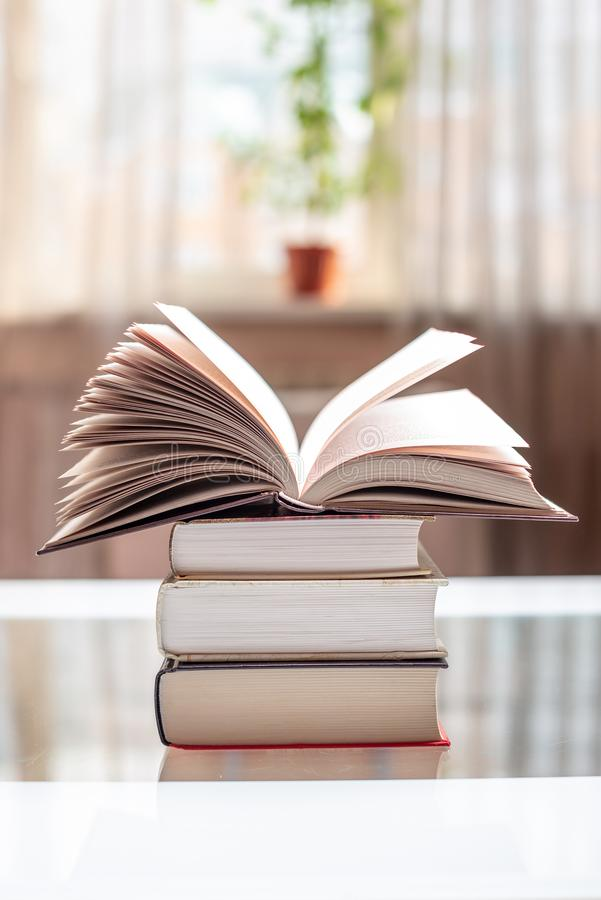 Open book on a stack of books on a table in a bright room. Education and reading of paper books stock photo