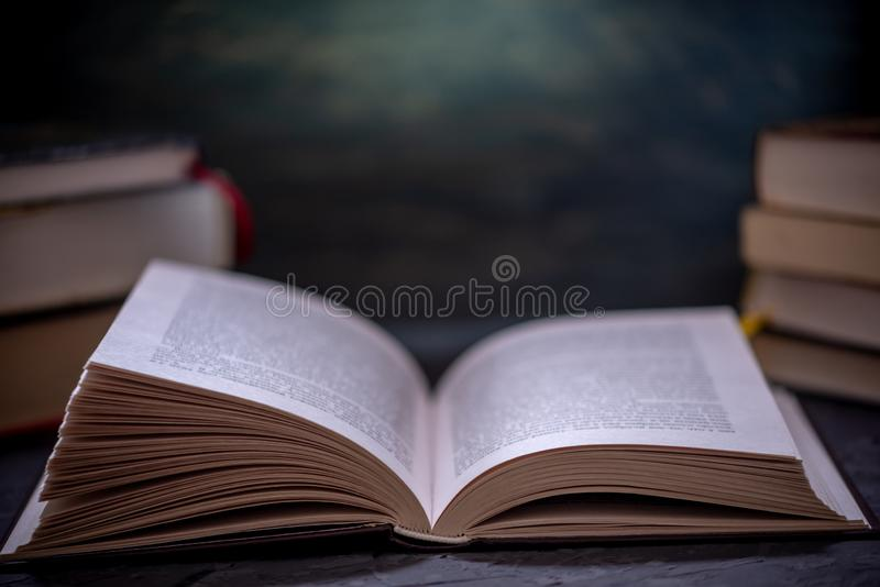 Open book on a stack of books on a table on a dark background. Education and reading of paper books stock photo
