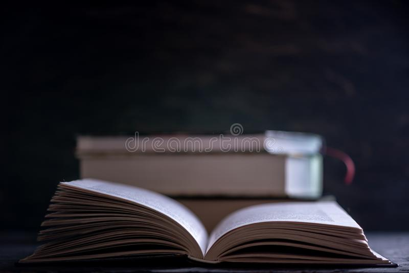 Open book on a stack of books on a table on a dark background. Education and reading of paper books royalty free stock images