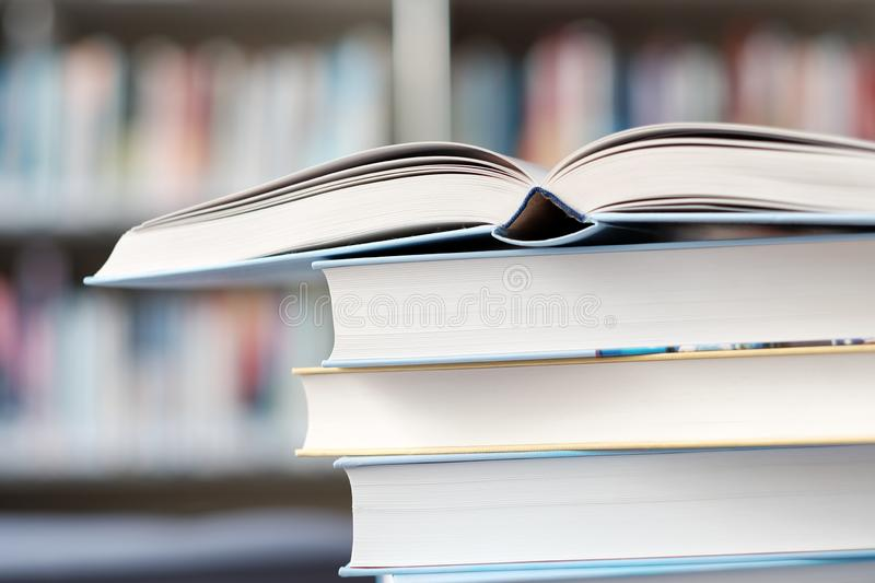 Open book on a stack of books on a table. In a library, shelf, read, white, education, study, school, learn, yellow, information, colledge, degree, student stock images