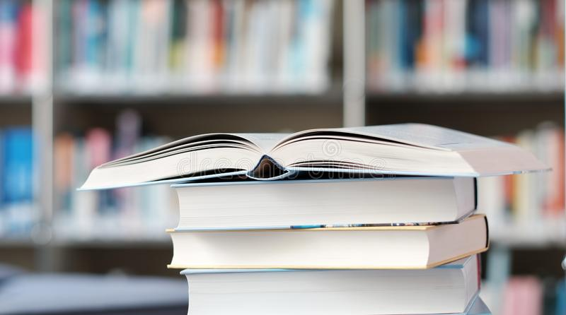 Open book on a stack of books in a library. Open book on a stack of books on a table in a library, shelf, read, white, education, study, school, learn, yellow stock image
