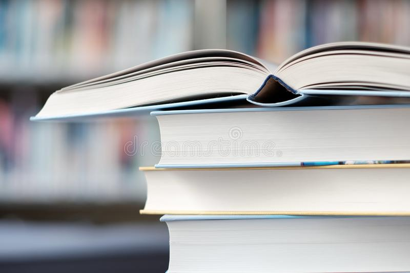 Open book on a stack of books in a library. Open book on a stack of books on a table in a library, shelf, read, white, education, study, school, learn, yellow stock photography
