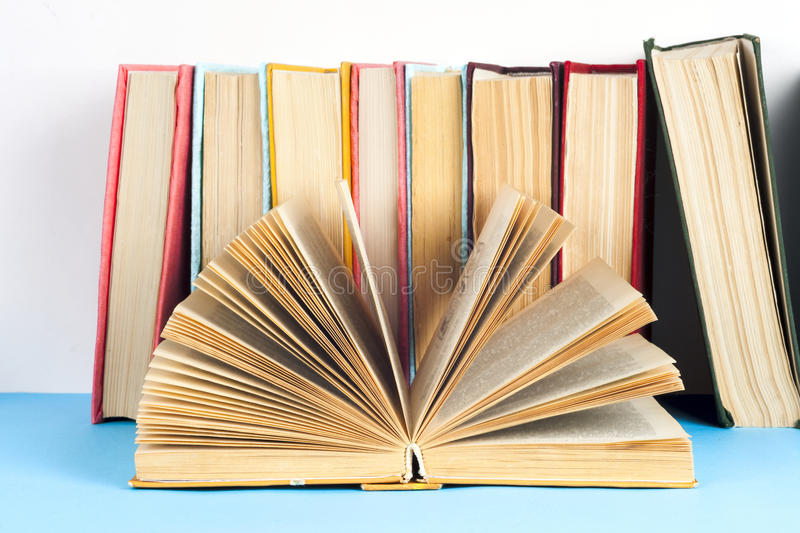 Open book, stack of colorful hardback books on light table. Back to school. Copy space for text stock photos