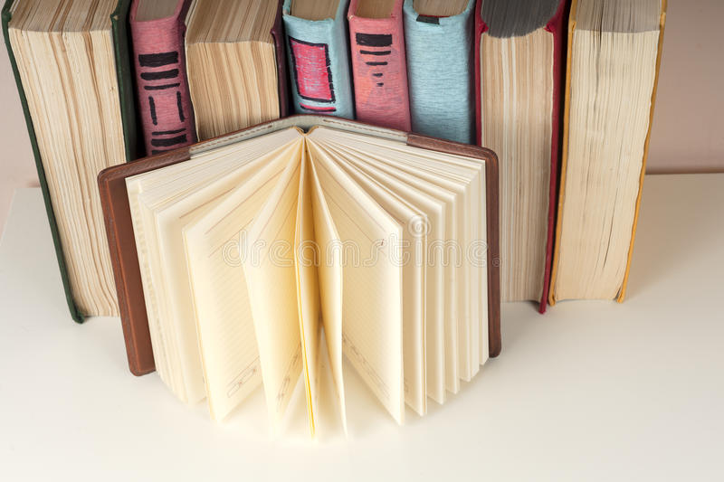 Open book, stack of colorful hardback books on light table. Back to school. Copy space for text stock images