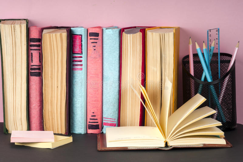 Open book, stack of colorful hardback books on light table. Back to school. Copy space for text royalty free stock photo
