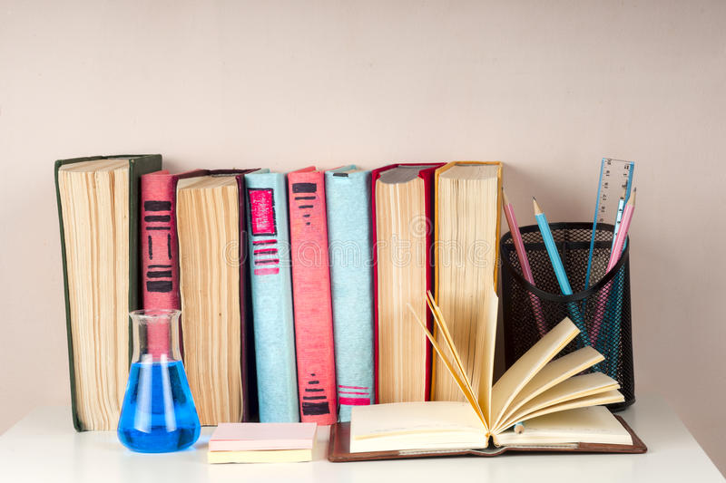 Open book, stack of colorful hardback books on light table. Back to school. Copy space for text stock photography