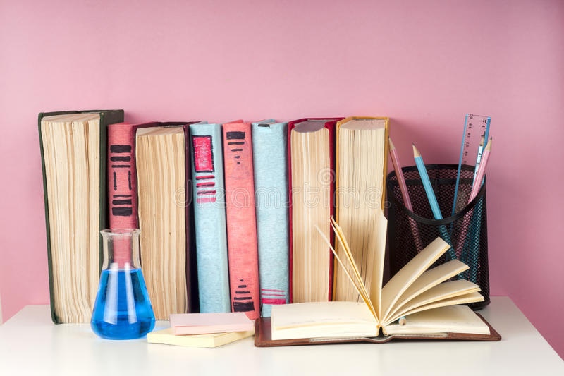 Open book, stack of colorful hardback books on light table. Back to school. Copy space for text royalty free stock images