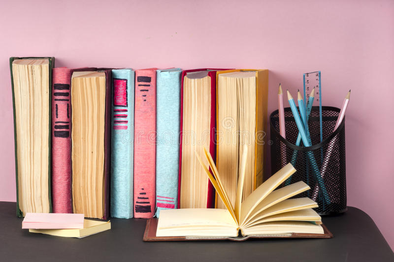 Open book, stack of colorful hardback books on light table. Back to school. Copy space for text stock photo