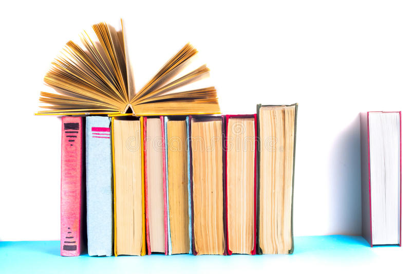 Open book, stack of colorful hardback books on light table. Back to school. Copy space for text royalty free stock image
