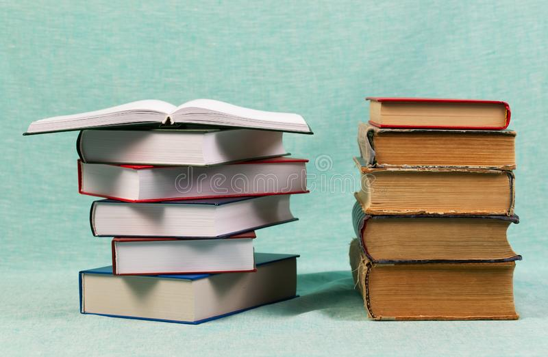 Open book, stack of hardback books on table. Back to school. Copy space stock photos