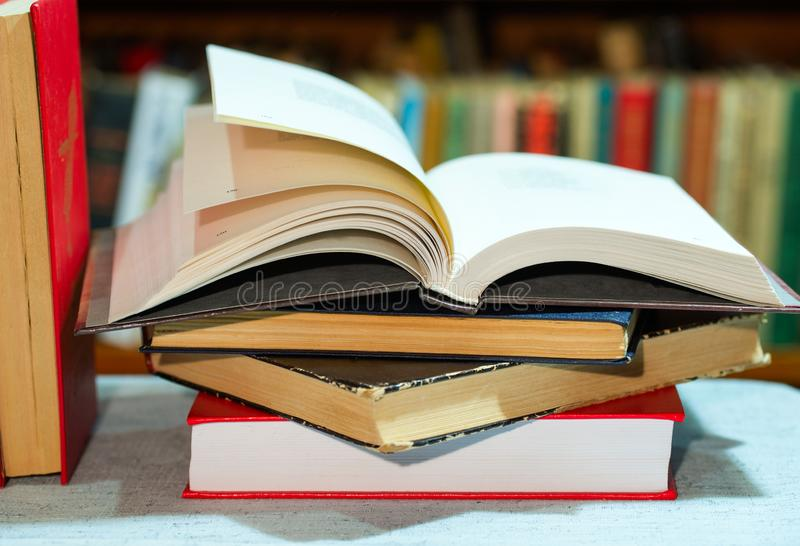 Open book, stack of hardback books on table. Top view. Open book, stack of hardback books on table. Back to school. Copy space. Top view stock image