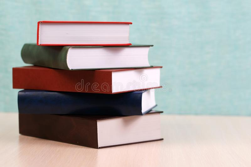 Open book, stack of hardback books on wooden table. royalty free stock photography