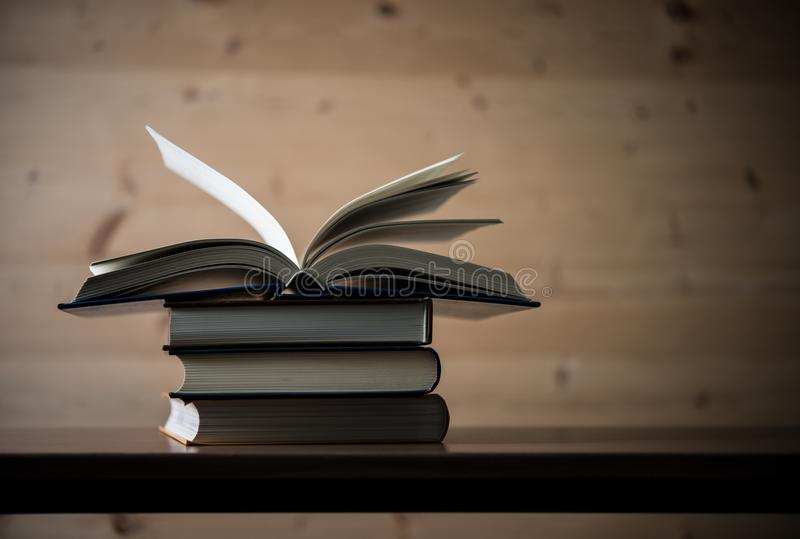 Open book, stack of hardback books on wooden table. Education co royalty free stock photo