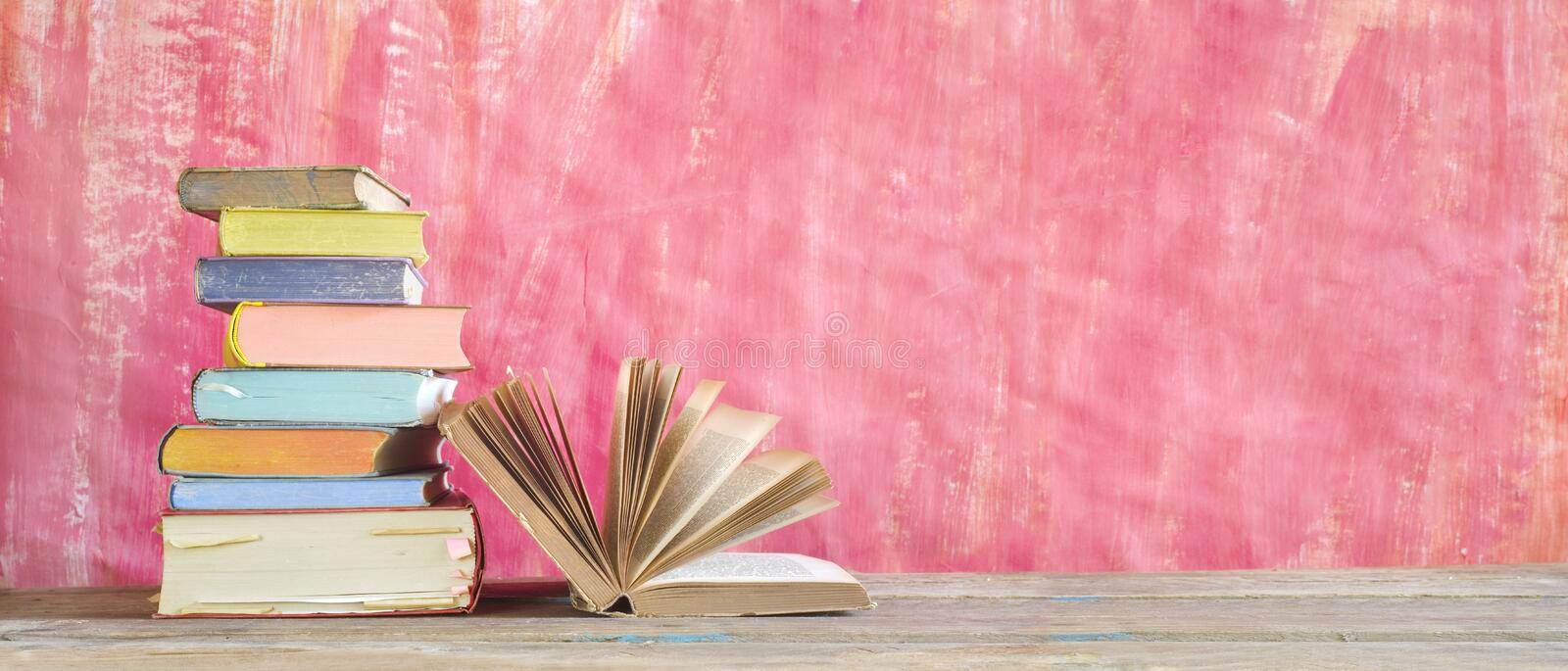 Open Book and stack of multicolored hardback books, reading education, literature,book fair concept. Panoramic format, copy. Open Book and stack of multicolored stock image