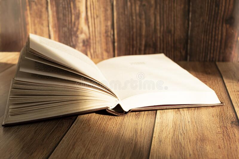 Open book on the table. A stack of old books with yellow pages. Book binding. Knowledge and education. stock photos