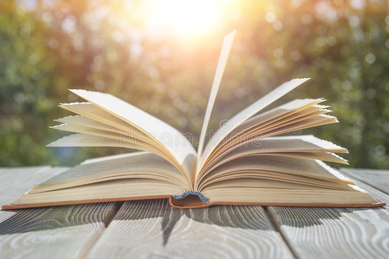 Open book on the table sunset background. royalty free stock photography