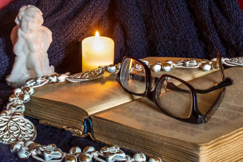 Celebration, still life., cozy homely atmosphere, evening, angel, candles, blanket, book, glasses, autumn, background, brown, cand. An open book, on which are royalty free stock images
