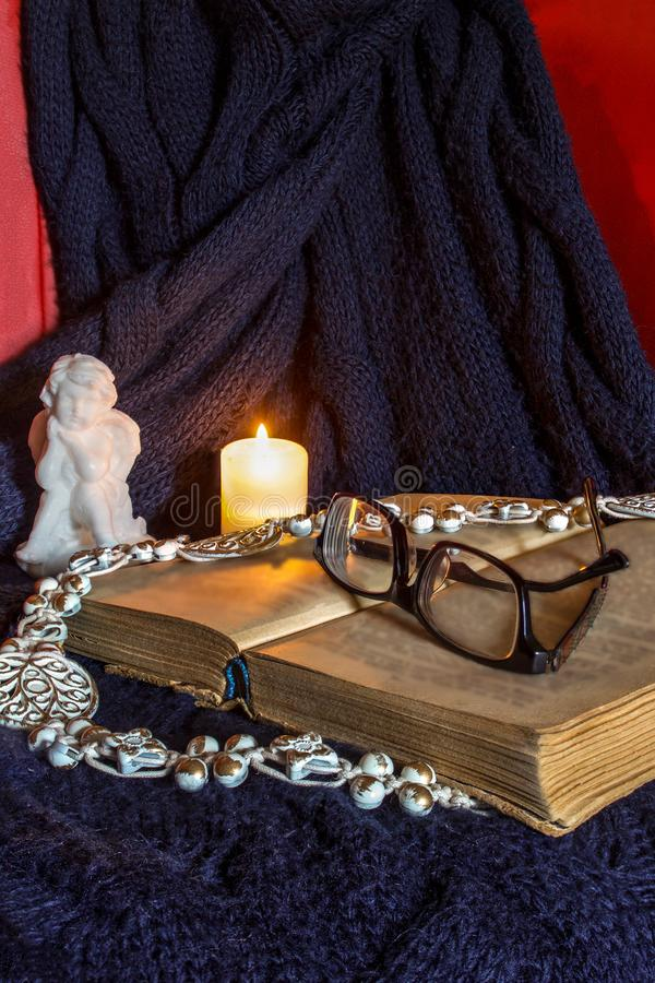 Celebration, still life., cozy homely atmosphere, evening, angel, candles, blanket, book, glasses, autumn, background, brown, cand. An open book, on which are stock image